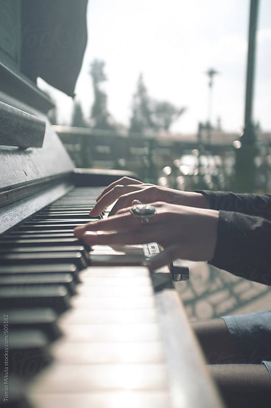 Girl playing on the piano by Tomas Mikula for Stocksy United