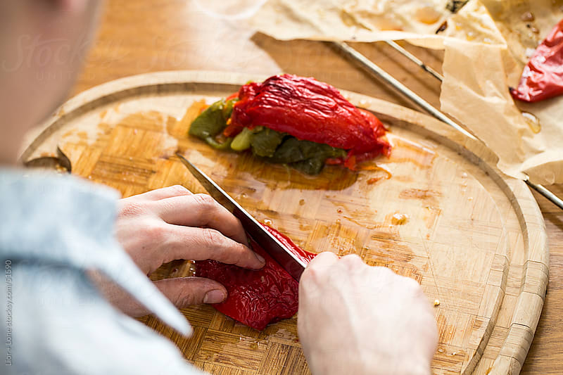 Man slicing roasted peppers on cutting board by Lior + Lone for Stocksy United