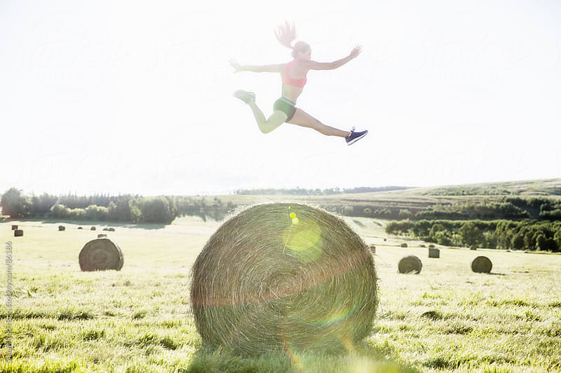 a fit young woman jumping over a hay bale by Shaun Robinson for Stocksy United