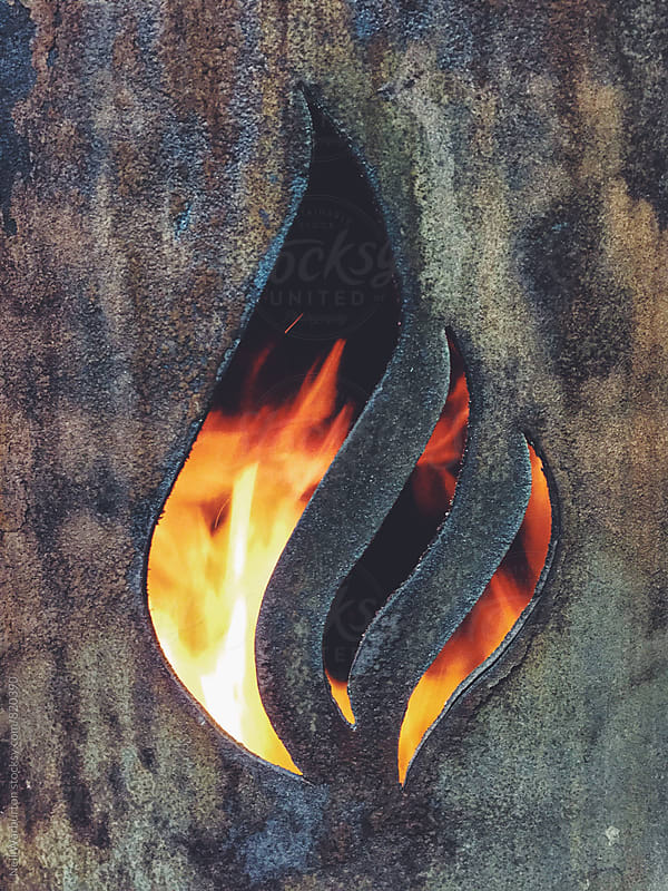 A flame symbol cut out from a stove with flames behind by Neil Warburton for Stocksy United