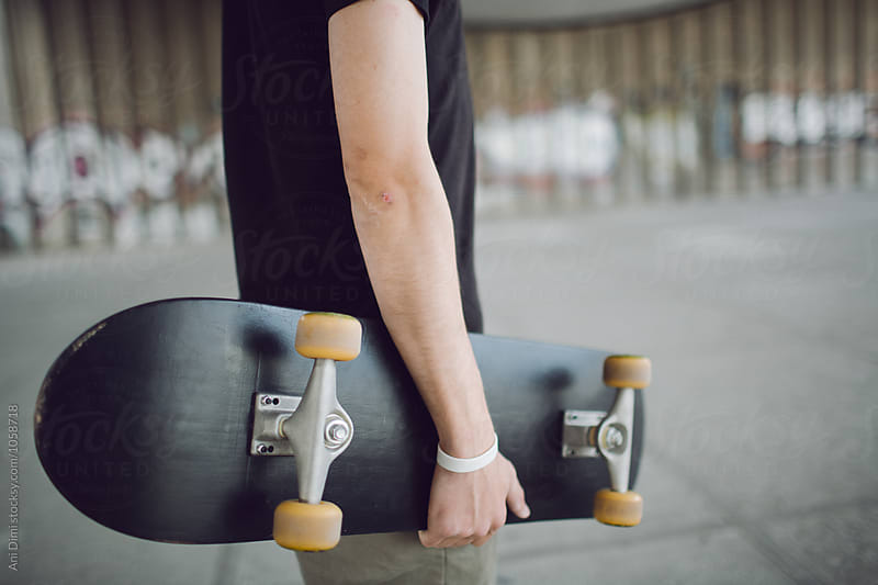 Skater holding his skateboard by Ani Dimi for Stocksy United