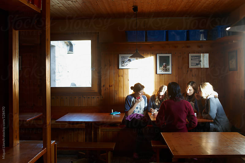 Group of women sitting and talking inside a wooden mountain hut by Miquel Llonch for Stocksy United