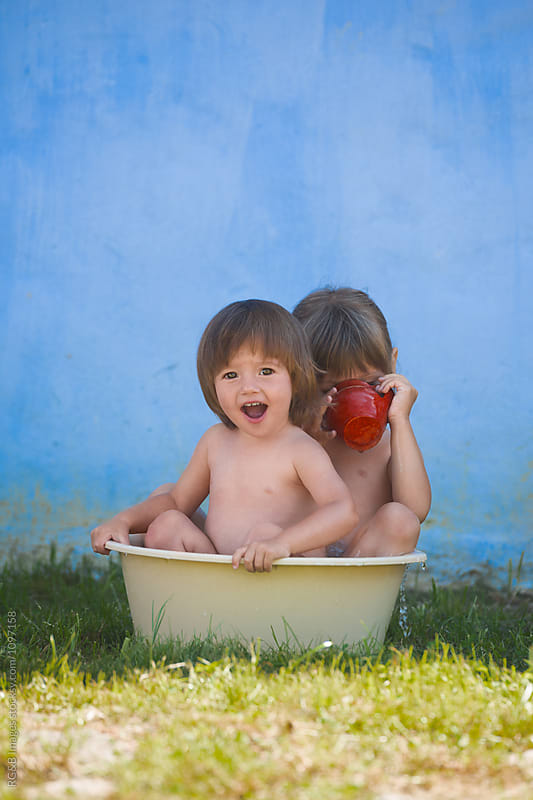 Cute little sisters bathing together in a plastic basin outdoor by RG&B Images for Stocksy United