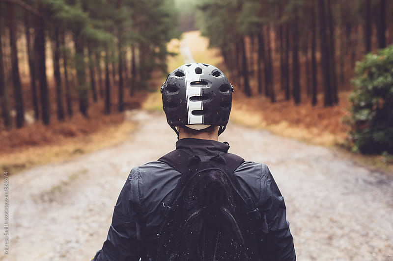 A mountain biker wearing a helmet, looking at the ride ahead by Maresa Smith for Stocksy United