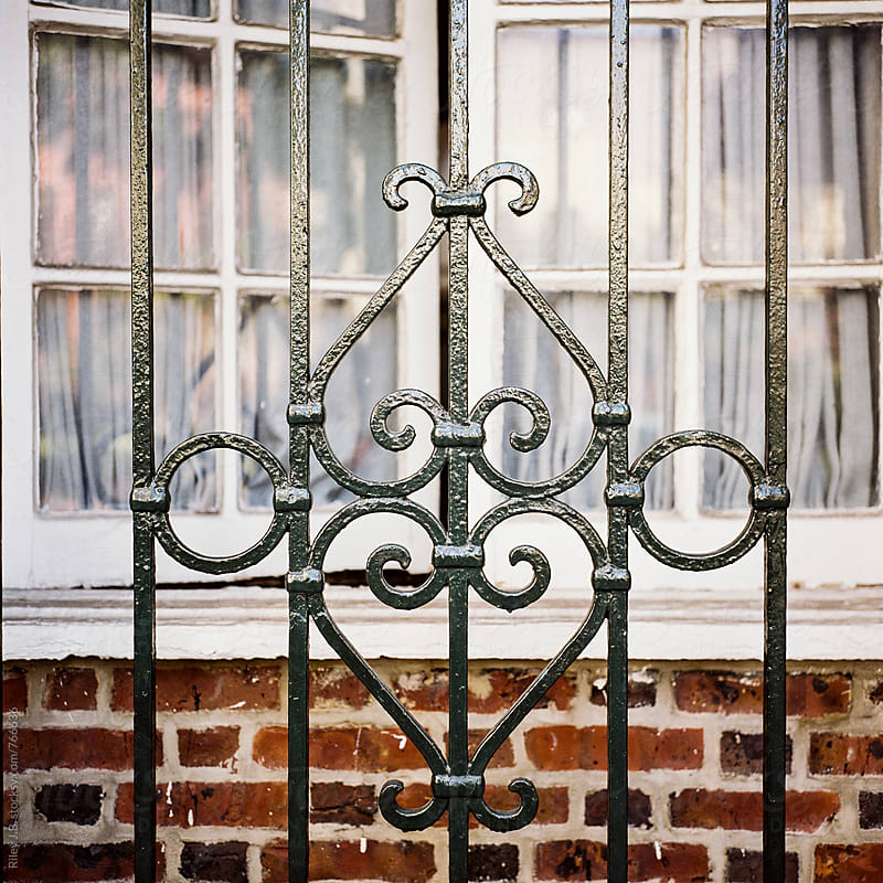 A ornate wrought iron fence in front of an open window by Riley J.B. for Stocksy United