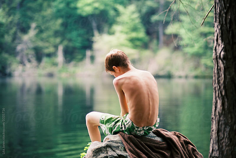 teen boy sitting on rock by a  lake by Léa Jones for Stocksy United