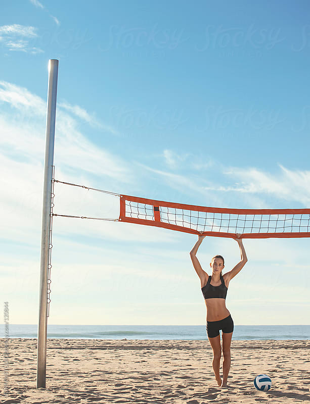 Beach volleyball. Sporty woman standing with ball and holding to the net. by BONNINSTUDIO for Stocksy United