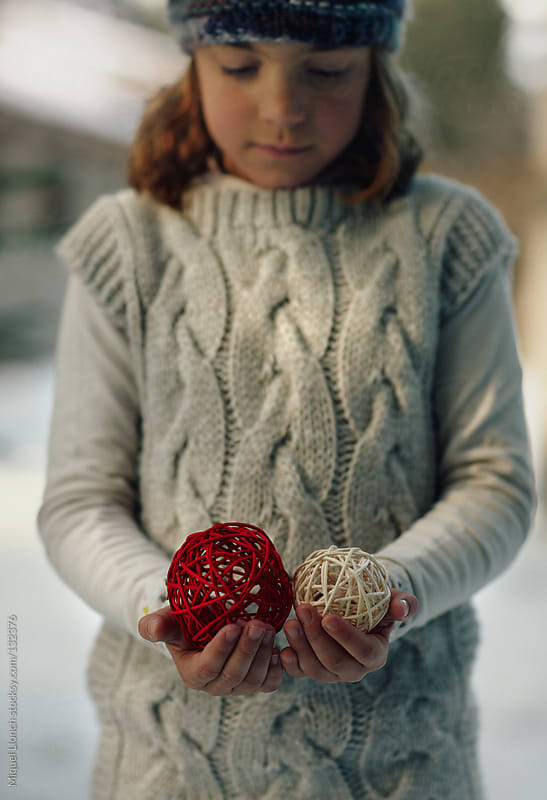 Little girl holding decorating balls by Miquel Llonch for Stocksy United