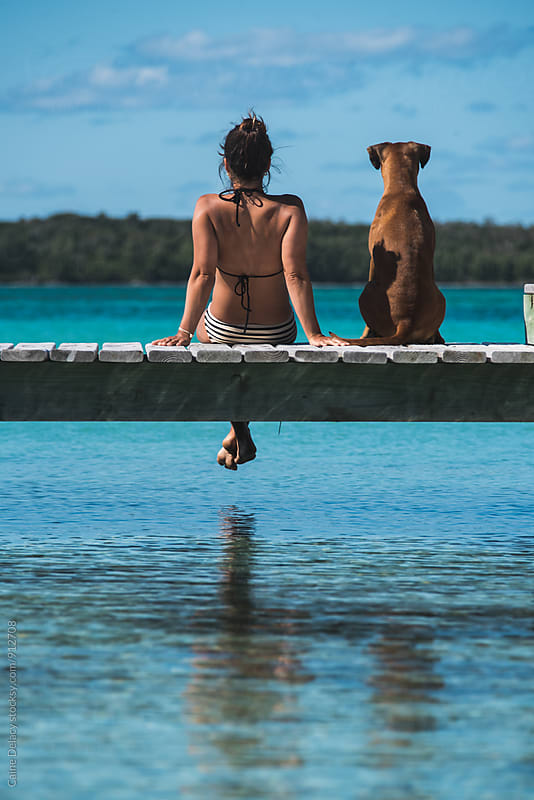 Gorgeous young woman in Bikini sittin gon Dock with Boxer puppy by Caine Delacy for Stocksy United