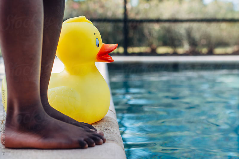 Black girl's legs next to a rubber duck by the swimming pool by Gabriel (Gabi) Bucataru for Stocksy United