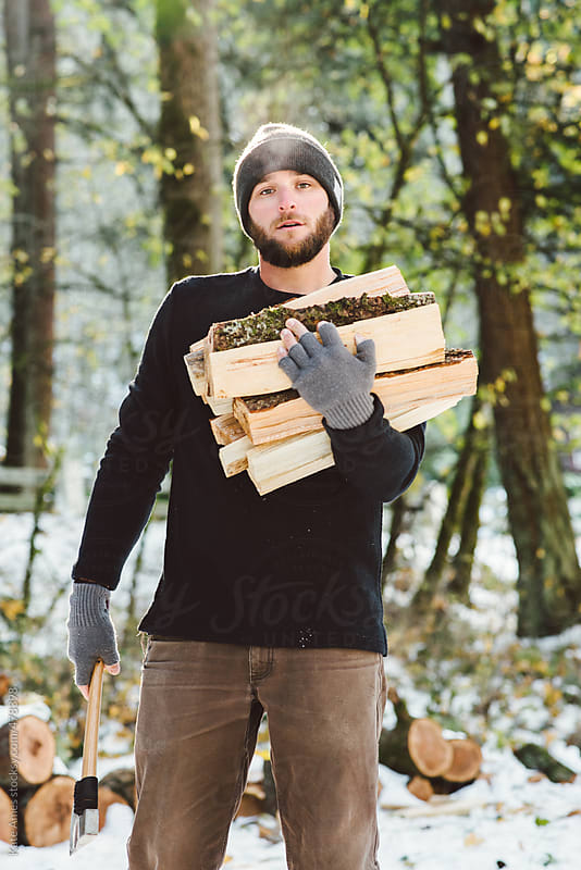 Man holding freshly chopped firewood and an ax outside in the snow. by Kate Daigneault for Stocksy United