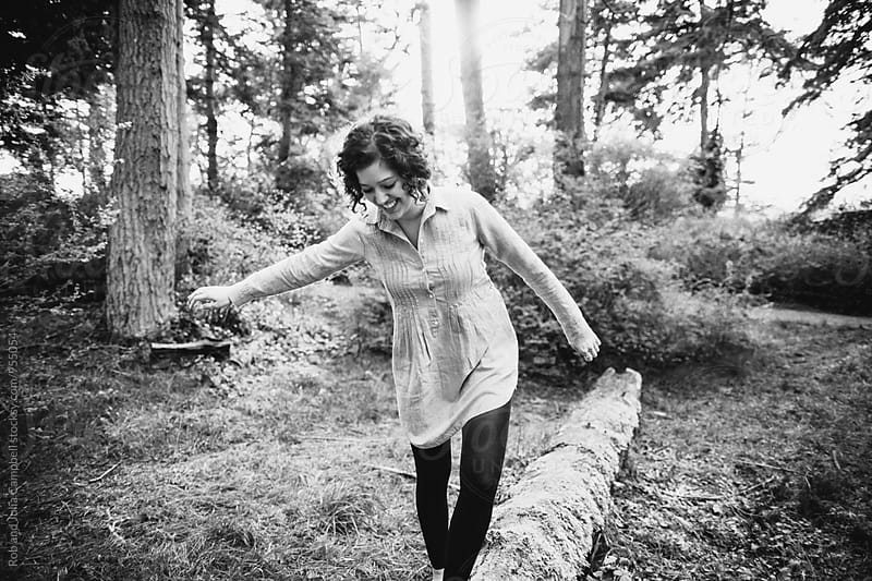 Portrait of young happy woman hanging out in nature - balancing on log by Rob and Julia Campbell for Stocksy United