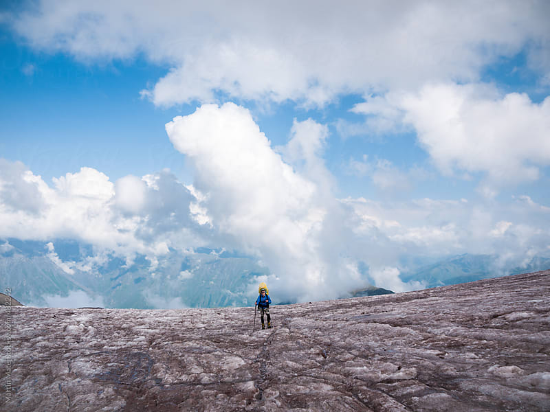Climber standing on dirty glacier with clouds floating around him by Martin Matej for Stocksy United