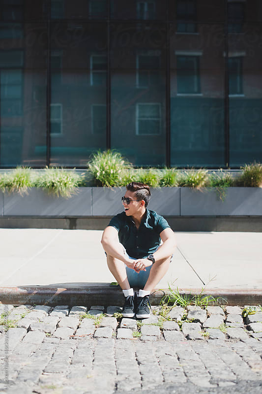 Handsome man sitting on curb on cobblestone in New York City by Lauren Naefe for Stocksy United