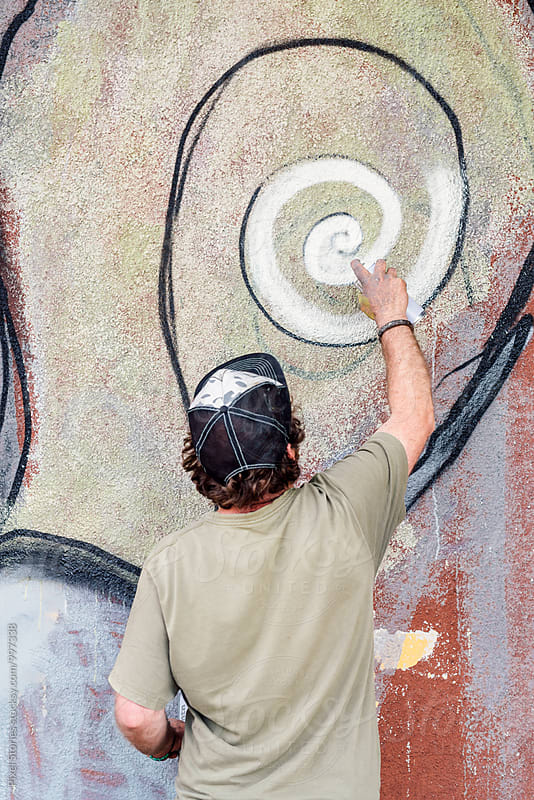 Male graffiti artist writing on wall by Pixel Stories for Stocksy United