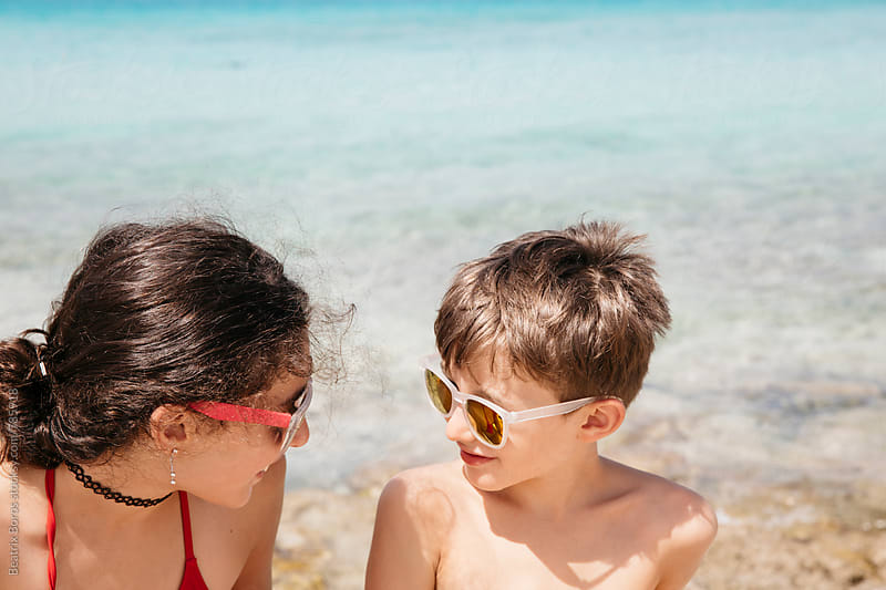 Siblings happily talking to each other by the sea by Beatrix Boros for Stocksy United