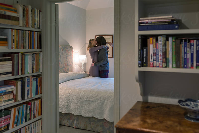 Intimate couple in bedroom. Viewed from the hall. by Paul Phillips for Stocksy United