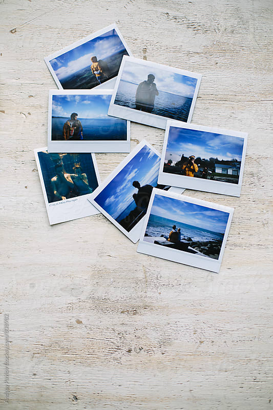 Instant photographs lying on white wooden desk by Andrey Pavlov for Stocksy United