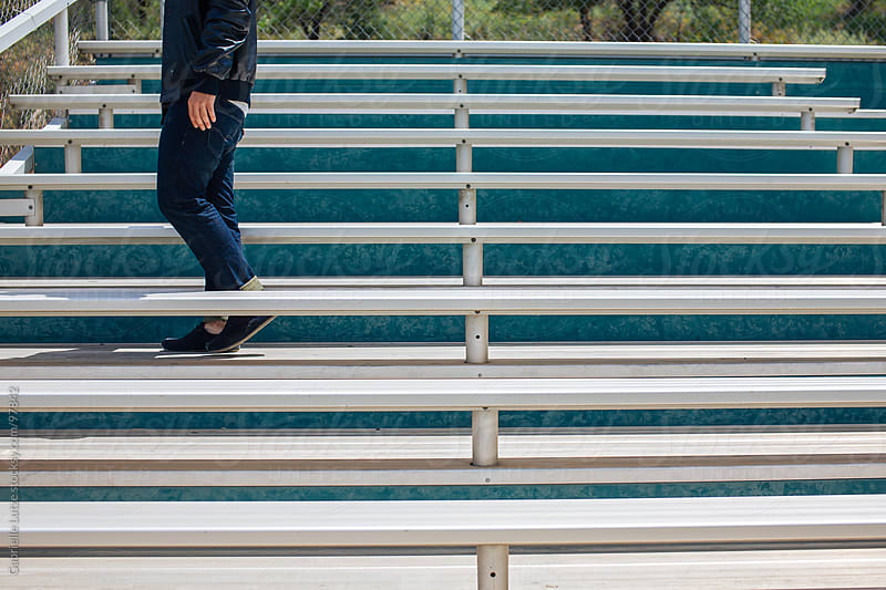 Man standing on bleachers by Gabrielle Lutze for Stocksy United