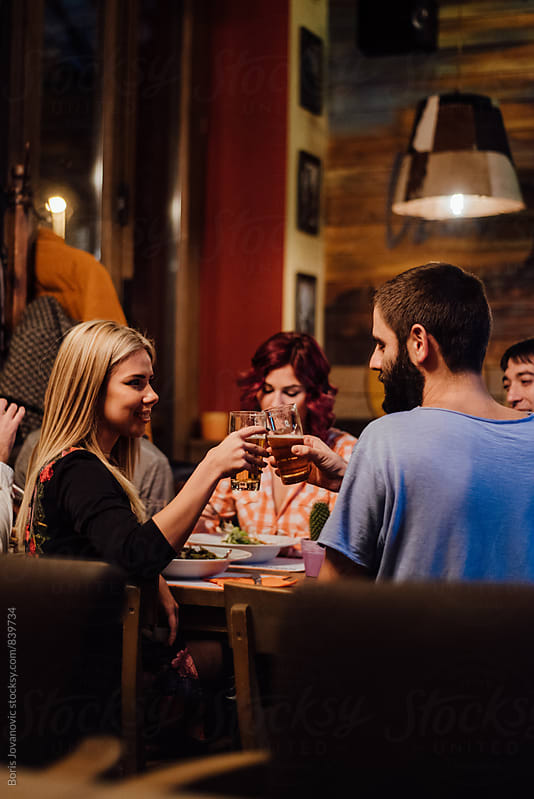 Friends cheersing in the restaurant by Boris Jovanovic for Stocksy United