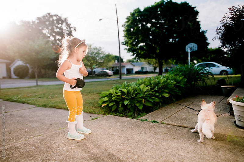 little girl walking dog by Maria Manco for Stocksy United