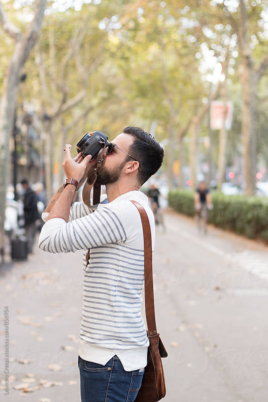 Young bearded man taking a pictures by Leandro Crespi for Stocksy United