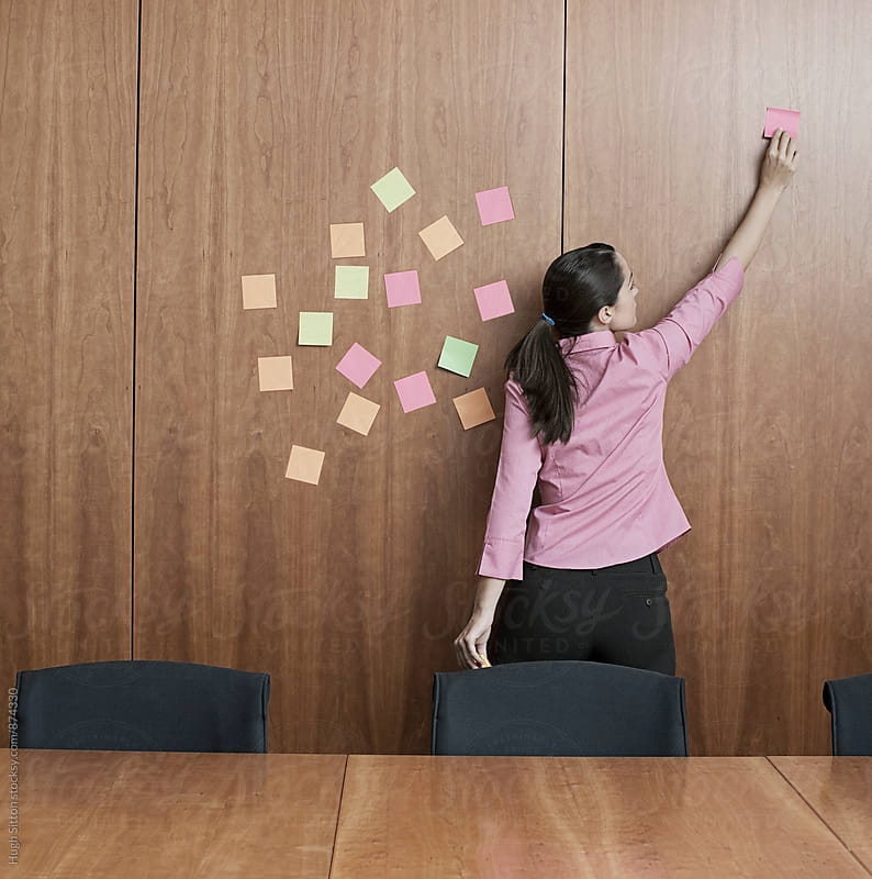 Businesswoman putting sticks on boardroom wall. by Hugh Sitton for Stocksy United