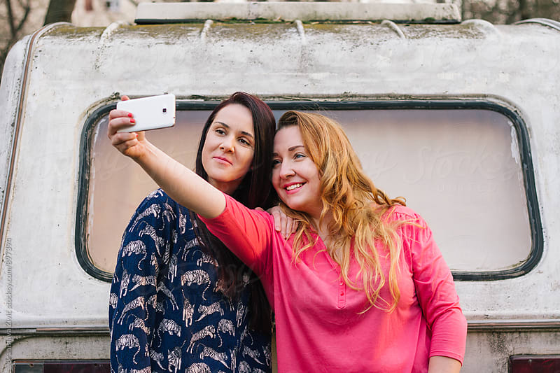 Two female model taking selphies and having fun by Evil Pixels Photography for Stocksy United