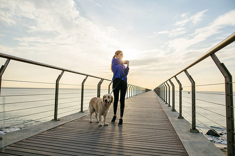 Runner woman doing stretching exercises near her dog at sunrise. by BONNINSTUDIO for Stocksy United