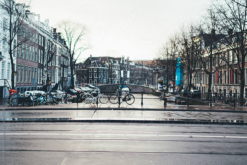 Wet streets by the canals of Amsterdam. by Javier Pardina for Stocksy United