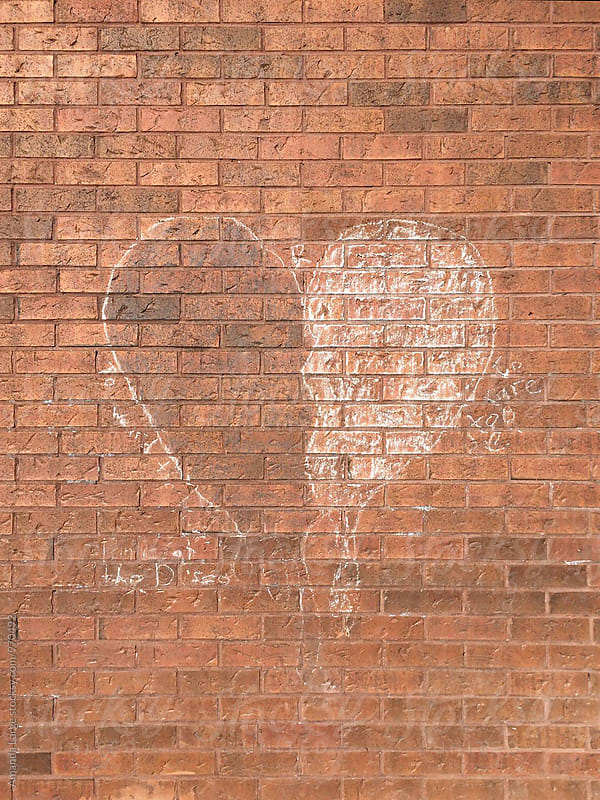 Chalk heart on a red brick wall by Amanda Large for Stocksy United