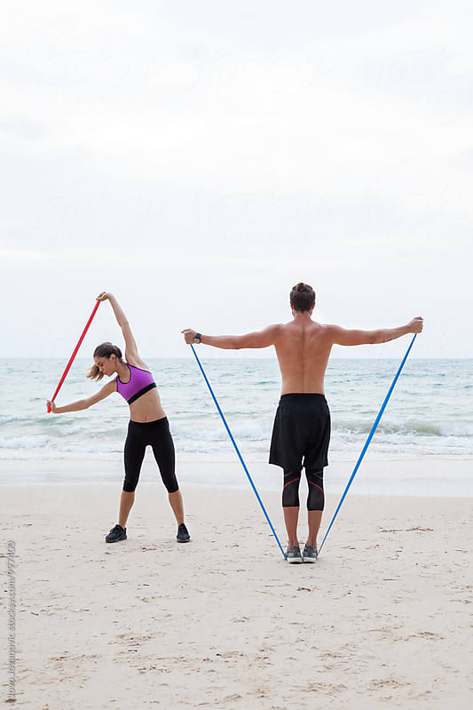 Fitness, sport, friendship and lifestyle concept - couple exercising at the beach by Jovo Jovanovic for Stocksy United