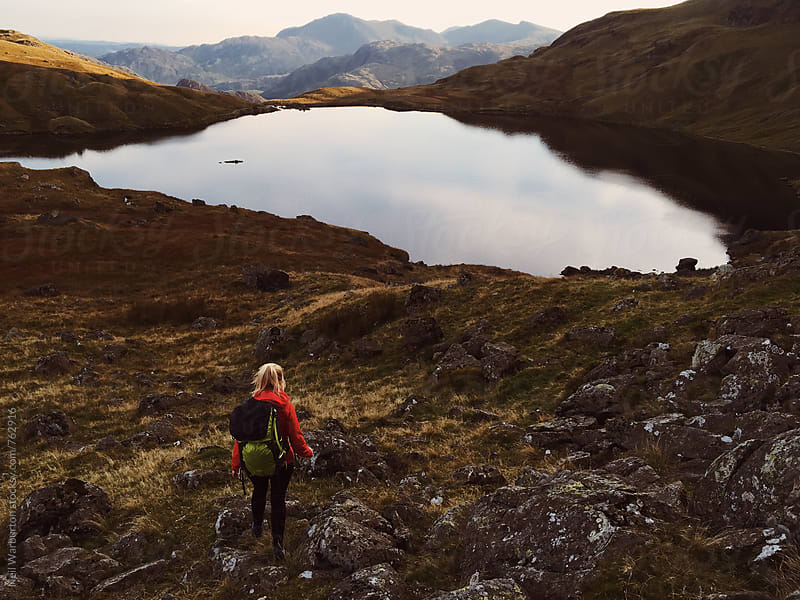 Female hiker approaching a mountain lake by Neil Warburton for Stocksy United
