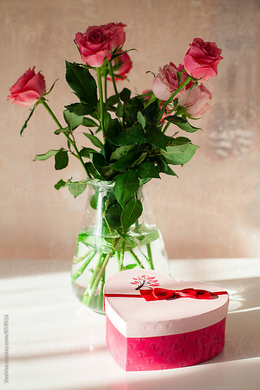 Valentine's gift and a bouquet of roses on the table  by Marija Mandic for Stocksy United