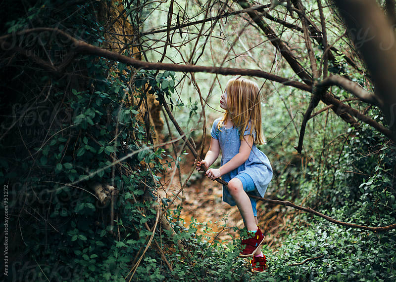 Little Girl sitting on Tree Branch by Amanda Voelker for Stocksy United