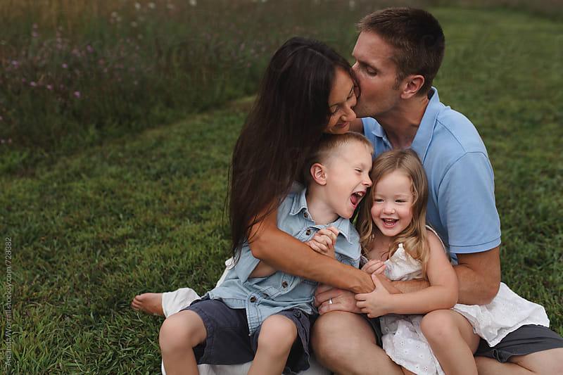 A happy family hugs outdoors by Amanda Worrall for Stocksy United