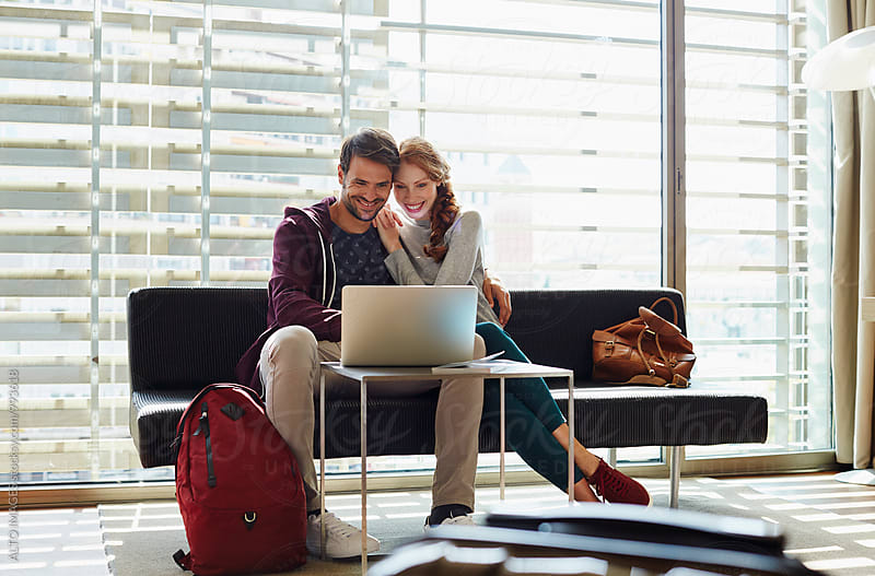 Happy Couple Using Laptop On Sofa In Hotel Room by ALTO IMAGES for Stocksy United