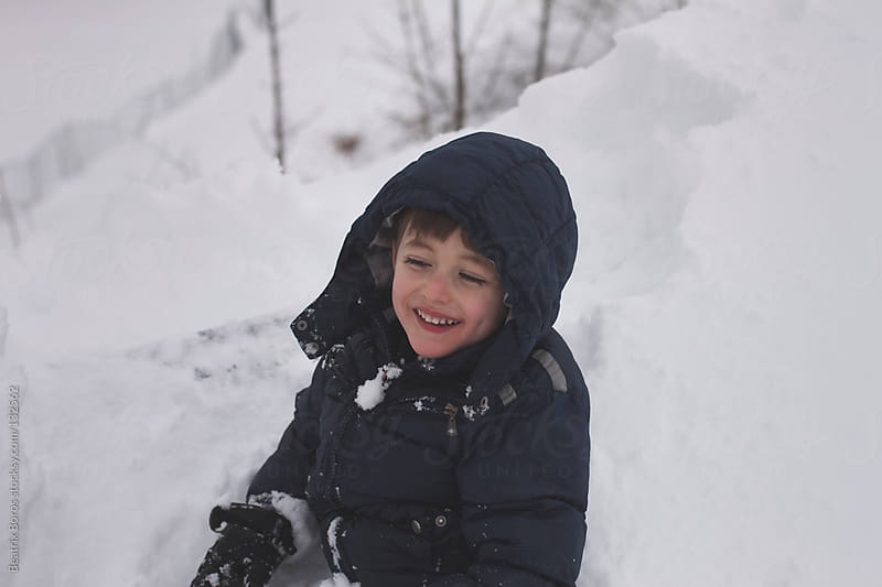 Little boy is having fun in the high snow by Beatrix Boros for Stocksy United