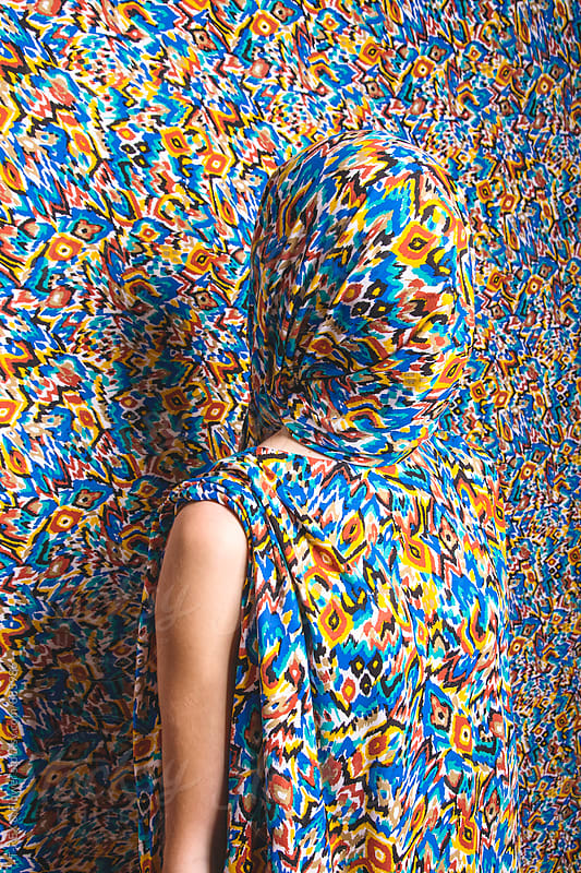 Close-up of woman covered with patterned colorful cloth by Danil Nevsky for Stocksy United