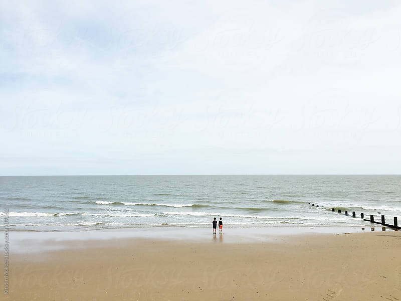 Two boys standing on the beach by Kirstin Mckee for Stocksy United
