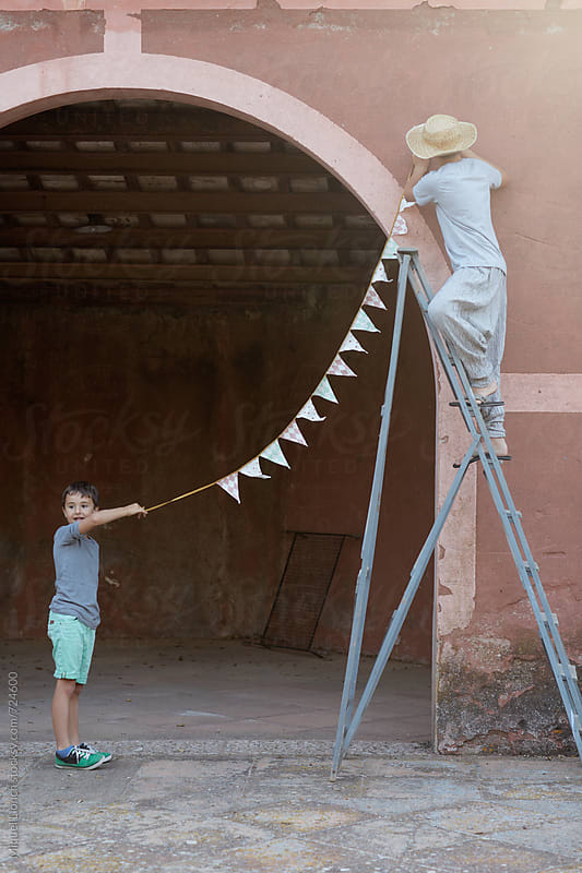 Two young men helping with the decoration of a party by Miquel Llonch for Stocksy United