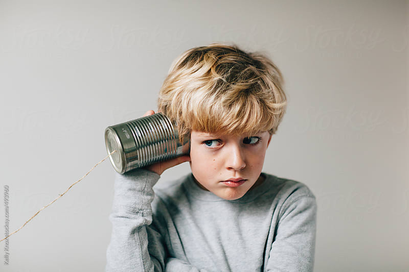 boy trying to listen through a tin can phone by Kelly Knox for Stocksy United