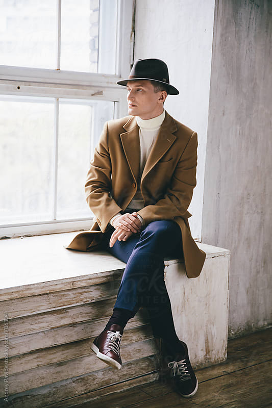 Stylish man sitting on a windowsill by Andrey Pavlov for Stocksy United