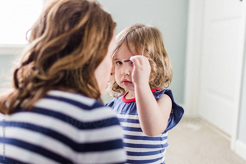 Mother and baby daughter playing with make up in the bedroom by Jakob for Stocksy United