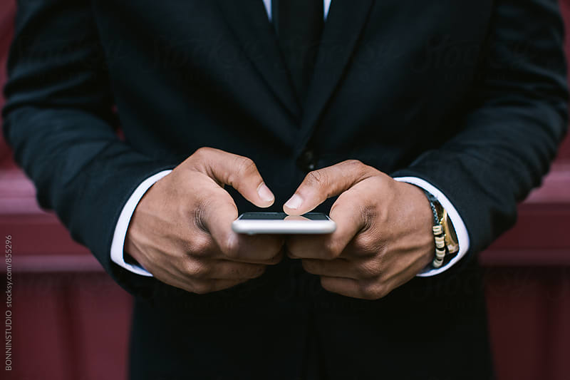 Closeup of hands of a businessman using his phone outside. by BONNINSTUDIO for Stocksy United