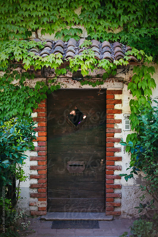 Wooden door decorated with old bricks amongst ivy leaves in ancient italian building by Laura Stolfi for Stocksy United