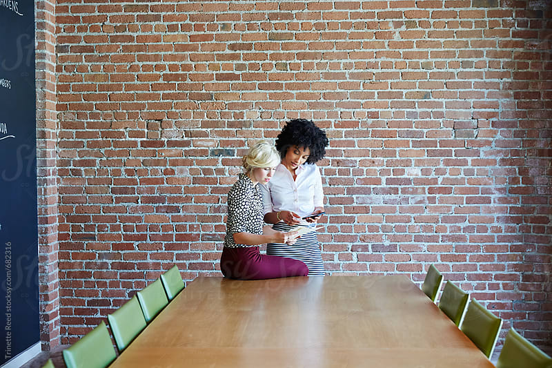 Two businesswoman meeting in conference room by Trinette Reed for Stocksy United