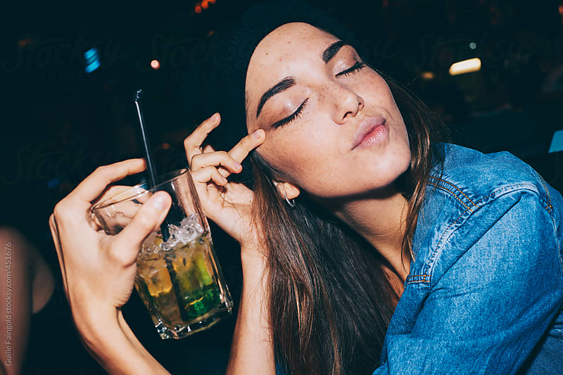 Girl with her eyes closed in a bar enjoying a mojito by Guille Faingold for Stocksy United