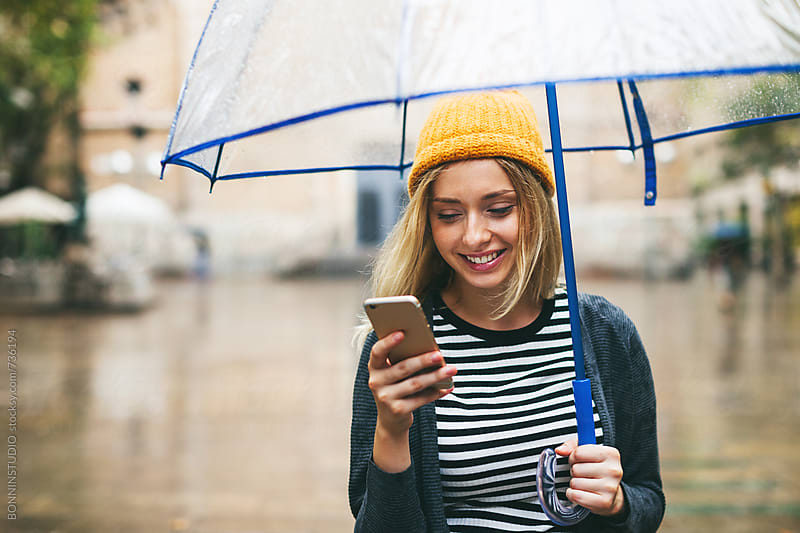 Smiling blonde woman using her smartphone on the street in a rainy day. by BONNINSTUDIO for Stocksy United