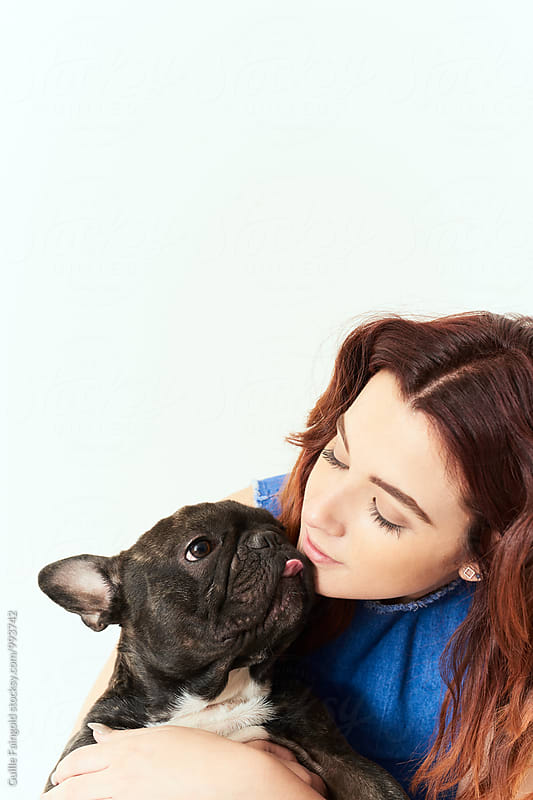 Girl and black bulldog pet sticking tongue out by Guille Faingold for Stocksy United
